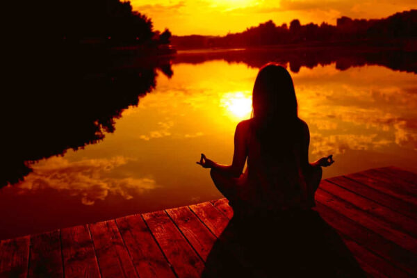 A girl is sitting near the water in a yoga posture during sunset