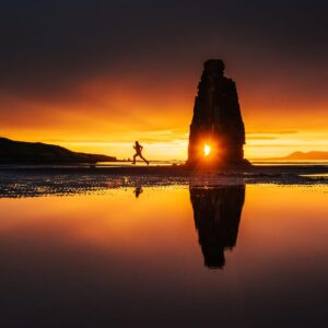 A man is running at beach at the time of sunset