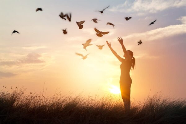 Woman standing in a grass field. Sunset and doves flying around her as she hold her arms up